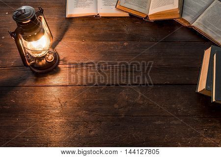 Old-fashioned kerosene lamp and opened books on the dark table in twilight