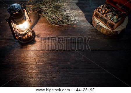Old-fashioned kerosene lamp and chest of jewelry on the dark table in twilight