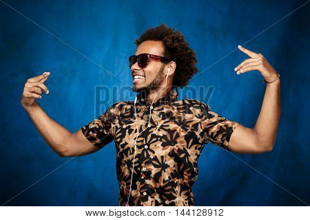 Young handsome african man in sunglasses listening music in headphones, dancing over blue background. Copy space.
