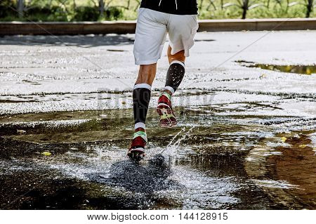 male athlete running in compression socks through a puddle water splashes