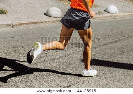 closeup muscular legs men running sport race on a city street
