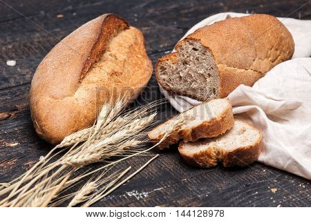 The macro view of rustic bread on an old vintage wooden table. Dark wooden background