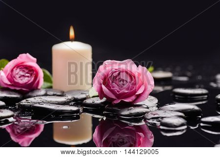 Two rose petals with candle and therapy stones