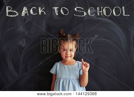 Little cute girl in a light-blue dress holding finger up against a blackboard