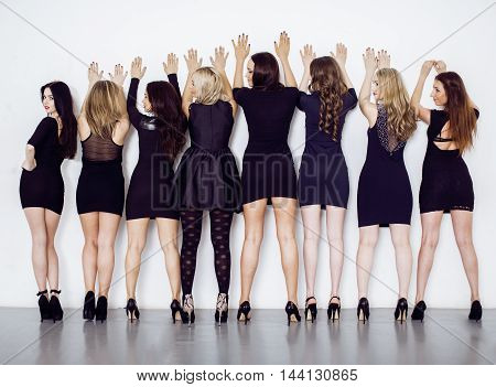 Many diverse women in line, wearing fancy little black dresses, party makeup, vice squad concept, lifestyle people
