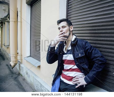 middle age man smoking cigarette on backjard, stylish tough guy, lifestyle people concept