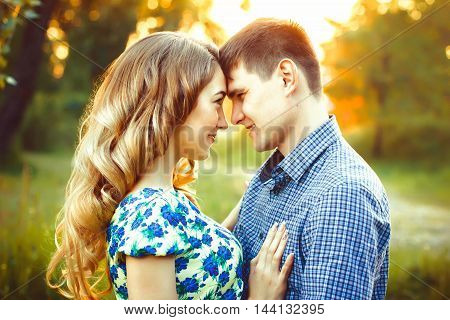 A loving couple looking at each other in the last rays of the sun in a field in the forest.