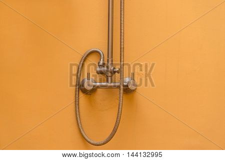 this is a silver shower handle on orange wall