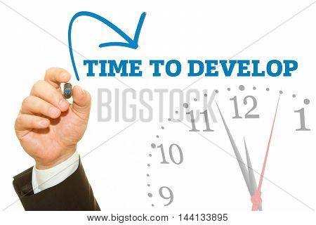 Businessman hand writing TIME TO DEVELOP message on a transparent wipe board.