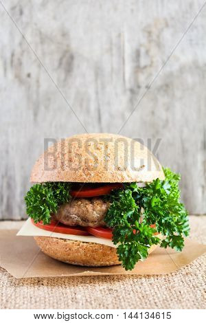 Homemade hamburger with tomatoes, cheese and fresh parsley, selective focus