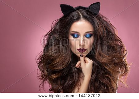 Beauty woman face with beautiful make-up color . Dark hair raised hair jewelry on his neck clean skin beautiful face the image of a cat . Portrait shot in studio on a pink background .