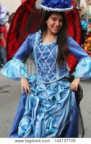 Cajamarca Peru - February 7 2016: Young woman in blue colonial dress poses in Carnival parade in Cajamarca Peru on February 7 2016