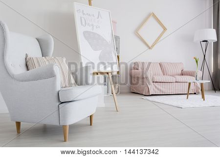 Spacious feminine living room with light armchair and upholstered sofa