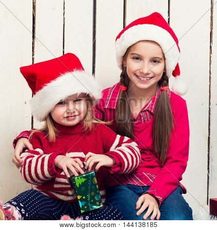 two little girls in red hats sitting on the floor with gifts near new year tree