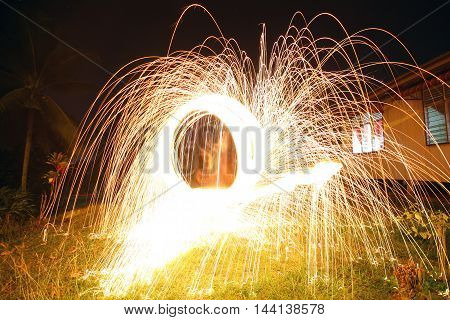 Burning steel wool. Showers of glowing sparks from spinning steel wool