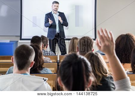 Confident lecturer is giving a speech to his students