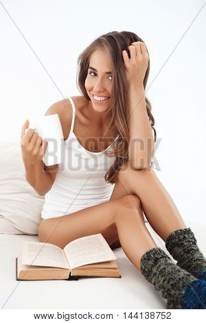 Young beautiful girl smiling, sitting on bed, drinking tea, reading book early in morning.