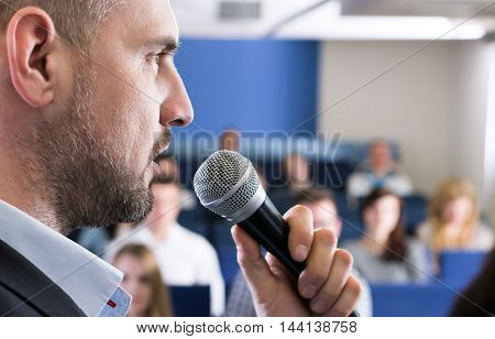 Focused lecturer is standing in aula with microphone in his hands