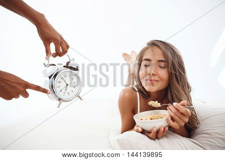 Hands showing time at alarm-clock to young beautiful girl lying on bed early in morning.