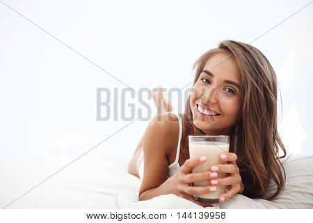 Young beautiful girl lying on bed, drinking coffee, smiling early in morning. Copy space.