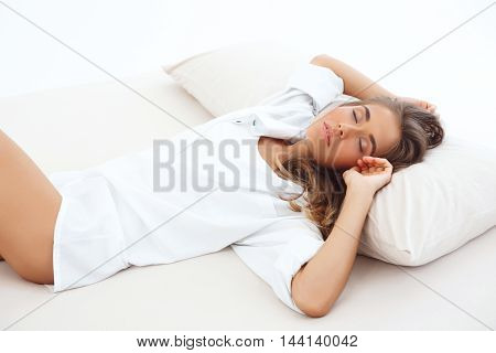 Young beautiful girl sleeping on bed early in morning.