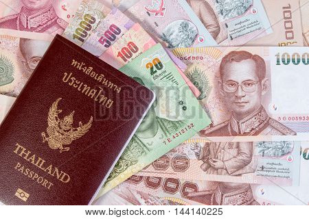 Thai Passport With Thai Money Banknote On Thai Money Background. The Passport Of Thai Citizen On Tha