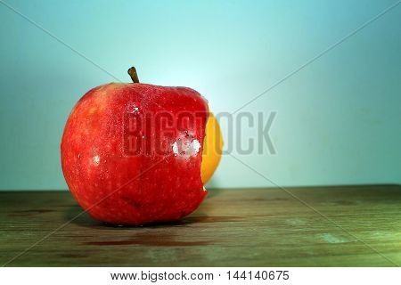 A Ripe Red Apple bitten with orange fruit on a wooden background