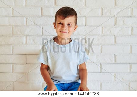 Portrait of smiling cute boy sitting on chair against white brick wall background