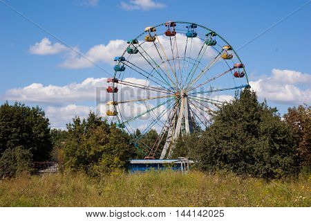 Big empty Ferris wheel in the park against the sky.