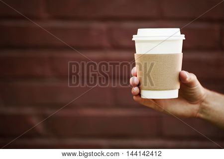 Paper cup of takeaway coffee in the hand. Place for your text or logo.