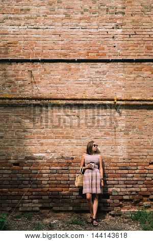 Portrait of young woman in dress and sunglasses leaning on brickwall with coffee cup