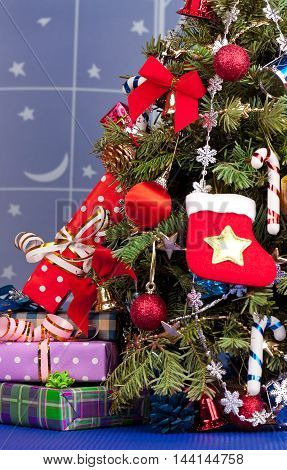 Christmas presents with garland over christmas spruce background