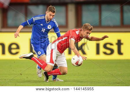 VIENNA, AUSTRIA - MARCH 31, 2015: Lukas Hiinterseer (#18 Austria) and Tino Susic (#14 Bosnien-Herzegowina) fight for the ball during an European Championship qualifying game.