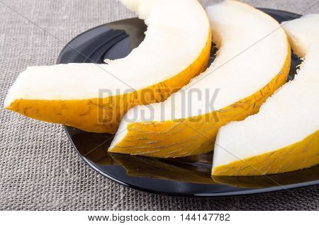Pieces Yellow Melon On A Black Plate