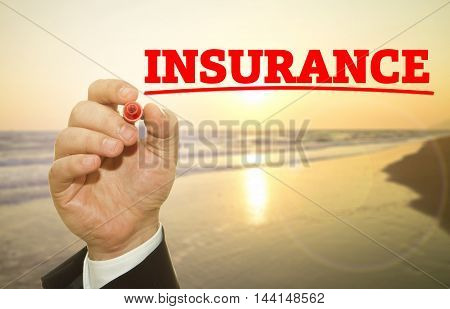 Businessman hand writing INSURANCE word on sunset
