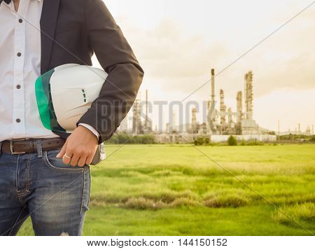refinery engineer with white safety helmet see drawing standing in front of oil refinery building structure in heavy petrochemical refinery industry.