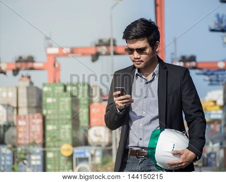 engineer used smartphone in construction worker checking location container on the background