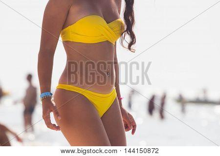 Beautiful girl on sunny tropical beach in bikini. Clouse up