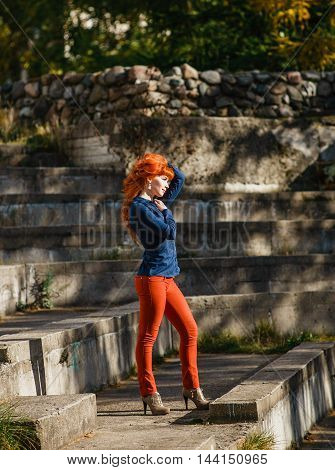 Beautiful young redhead woman smiling and holding her hands in her hair with hear eyes. Girl clothed in blue skirt, red pants. Autumn fashion concept.