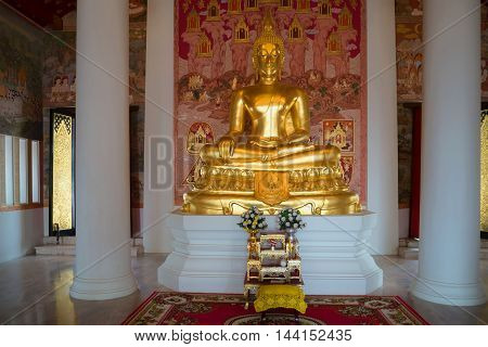 SUKHOTHAI, THAILAND - JANUARY 10, 2014: Sculpture of a sitting Buddha in the interior of a modern Buddhist temple. Religious landmark  of the city Sukhothai