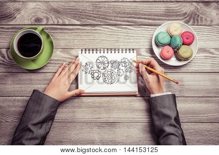 To view of businesswoman hands drawing in notepad gears mechanism