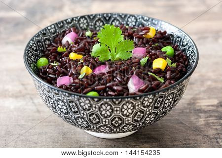 Black rice in a bowl and vegetables on wooden table