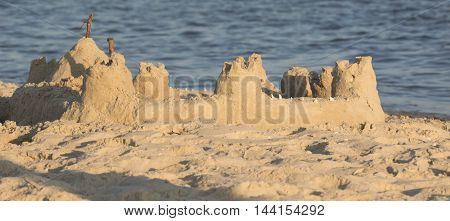 Built House sand castle with towers on the south shore of the sandy beach sea