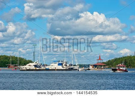 LAPPEENRANTA, FINLAND - AUGUST 8, 2016: Boat floats near pavilion on the small pier with yachts on The Saimaa Lake