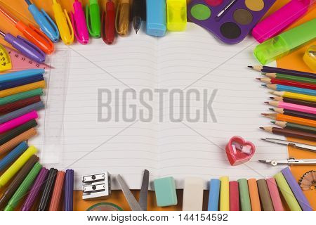 Different school supplies are around white blank notebook.