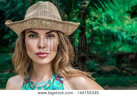 Portrait of beautiful young woman with straw hat on a sunny day looking into the camera over palm trees background. Beautiful eyes closeup of pretty girl wearing bikini and straw hat over green