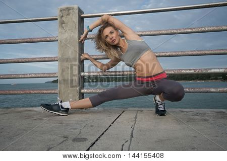 Young pretty blonde female wearing exercise clothing stretching on the pier near the sea and enjoying early morning with beautiful sunrise