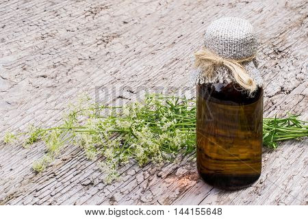 Medicinal plant Galium mollugo common name hedge bedstraw or false baby's breath and pharmaceutical bottles on old wooden table