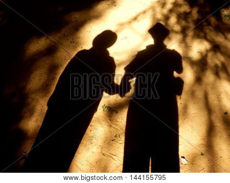 Eerie picture of a shadow couple holding hands on sandy ground