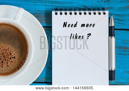 Need More Likes written on notepad near cup of morning coffee at blue table.
